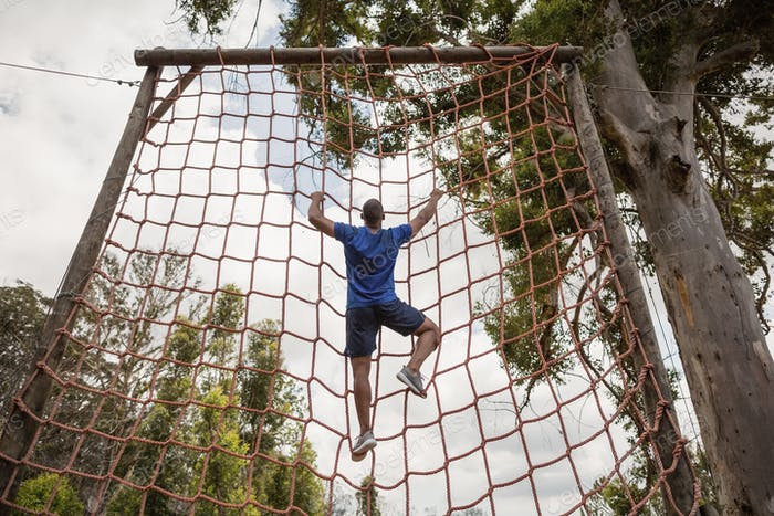 Fit man climbing a net during obstacle course