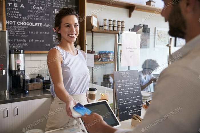 Customer at coffee shop pays smiling waitress with card