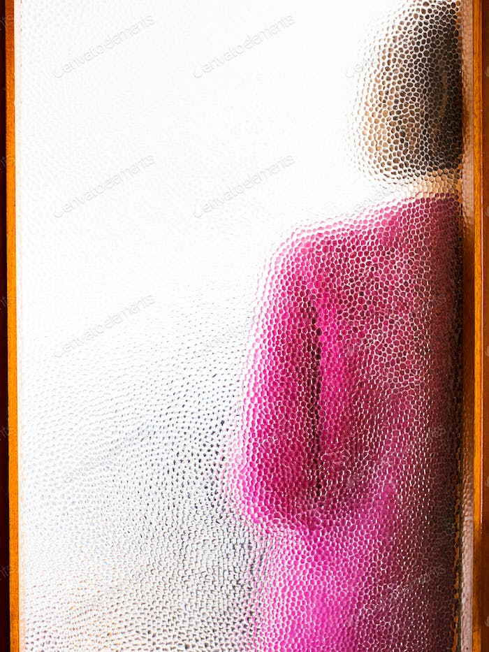 Young woman behind closed door seen through glass