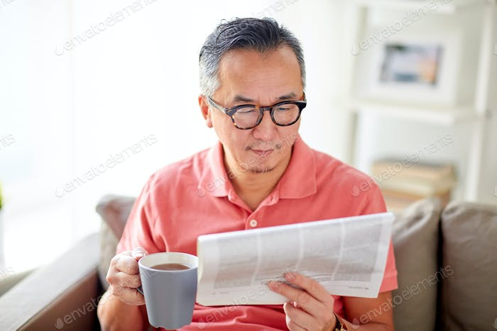 man drinking tea and reading newspaper at home