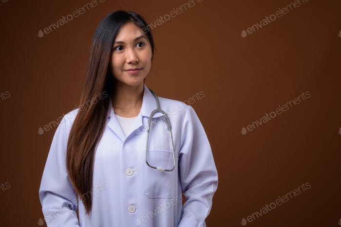 Young beautiful Asian woman doctor against brown background