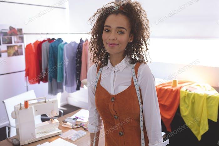 Junge Mixed-Race weibliche Modedesignerin steht im Designstudio am Tisch.