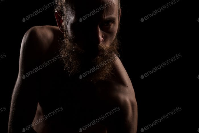 Angry hipster in dramatic photo on black background