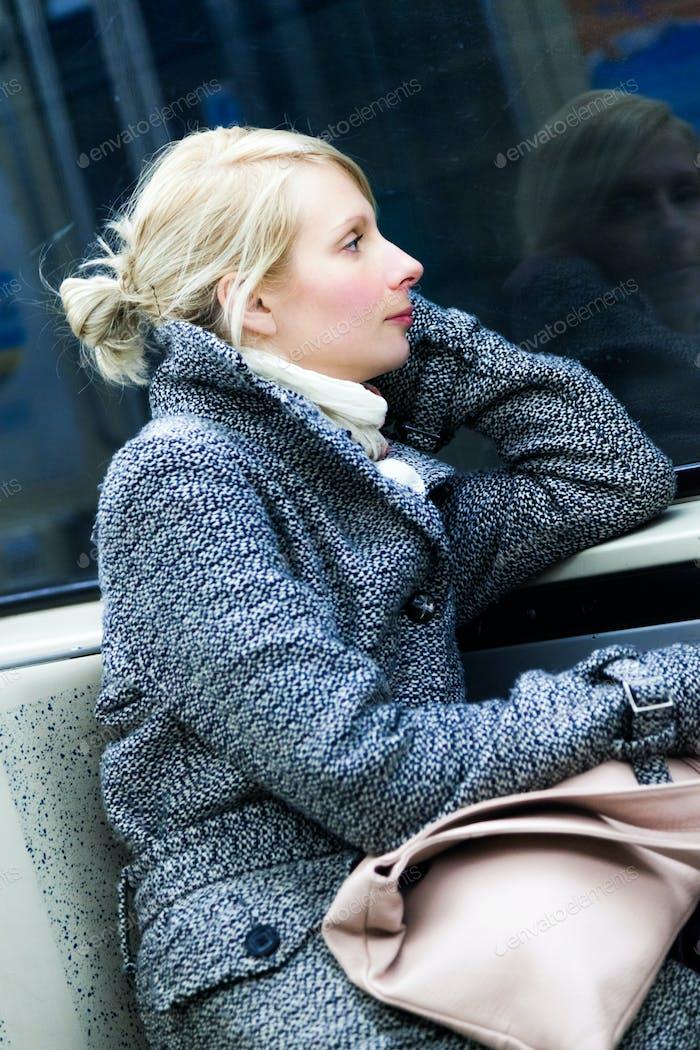 Junge Frau sitzt in einem Metro Wagon