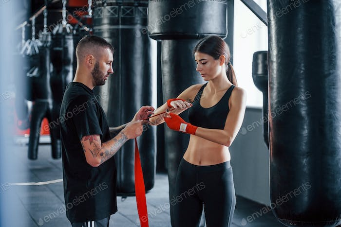 Wearing bandages. Young tattooed boxing coach teaches young woman in the gym