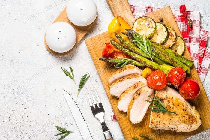 Chicken breast grilled with vegetables on a wooden serving board