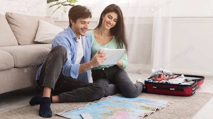 Loving couple planning vacation trip and using tablet