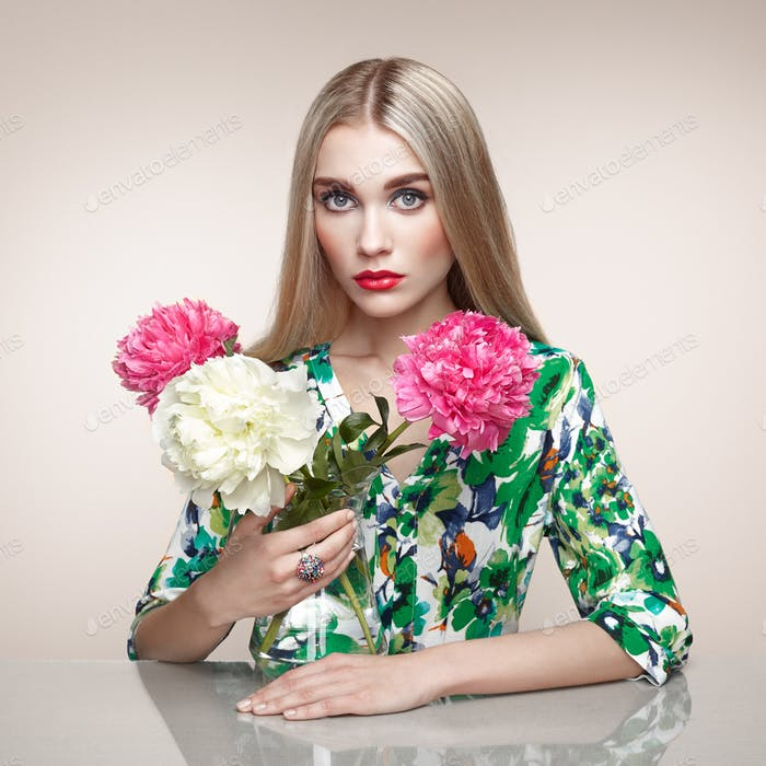 Fashion portrait of elegant woman with summer flowers