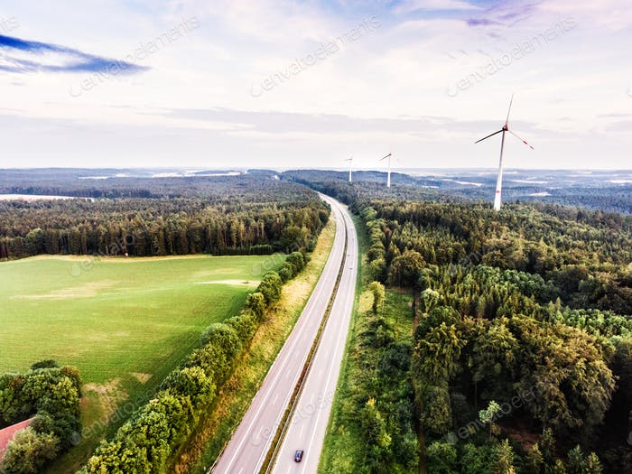 Highway in green forest, windmills, cloudy sky. Netherlands