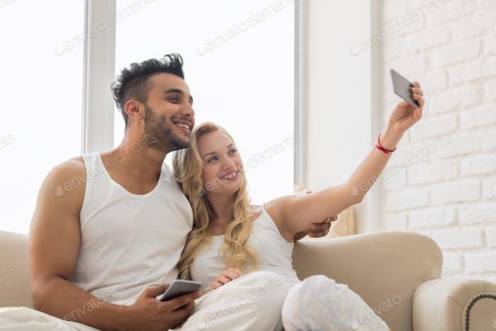 Junge Schöne Paar sitzen auf Trainer Fenster, Nehmen Selfie Foto Auf Handy Smartphone Glückliches Lächeln
