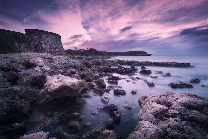 Meereswellen mit Felsen am Strand bei Sonnenuntergang