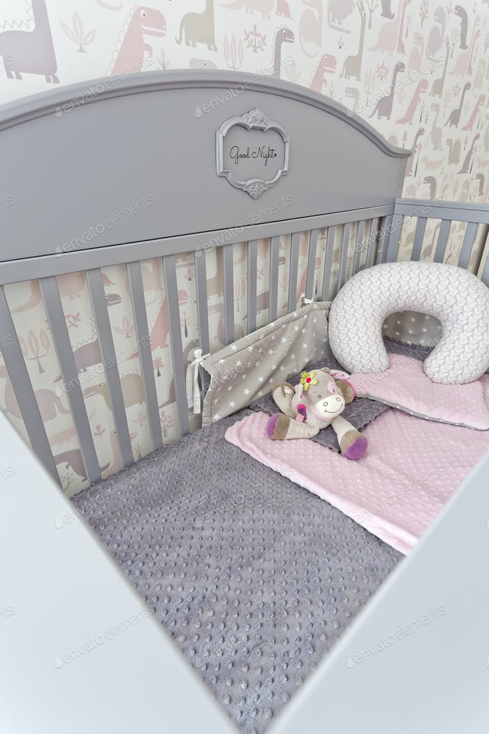 Stylish grey baby cot with toy