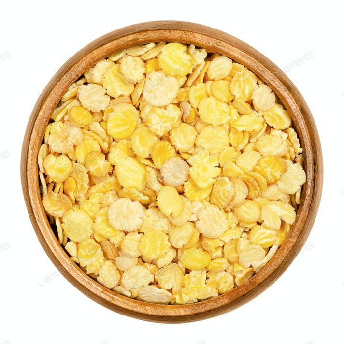 Soya flakes, soy flakes in wooden bowl over white