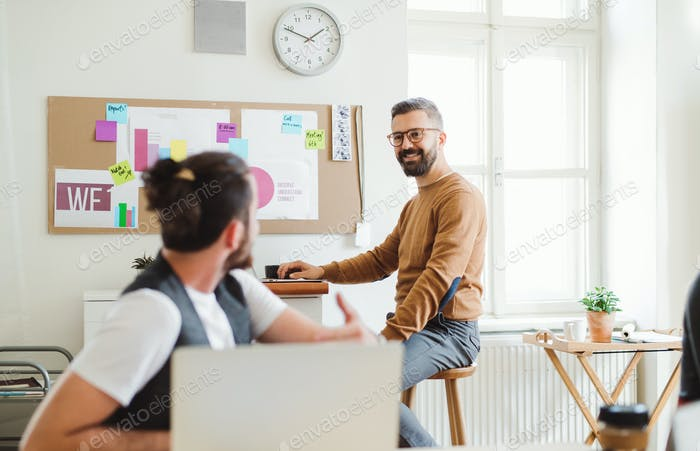 Two young male businesspeople with laptop talking in a modern office.