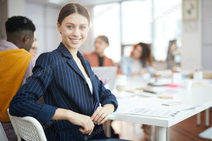 Улыбающаяся деловая женщина позирует в производственном Агентство