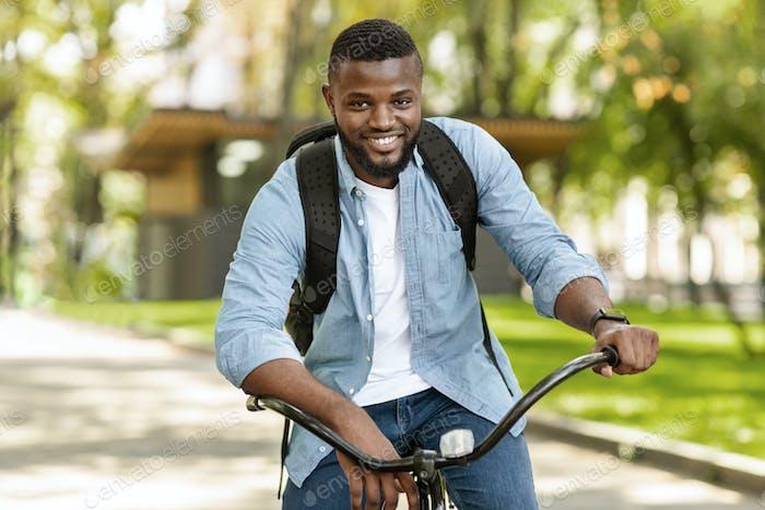 Porträt von gut aussehend Afro Mann Reiten Fahrrad im Freien, zur Arbeit gehen
