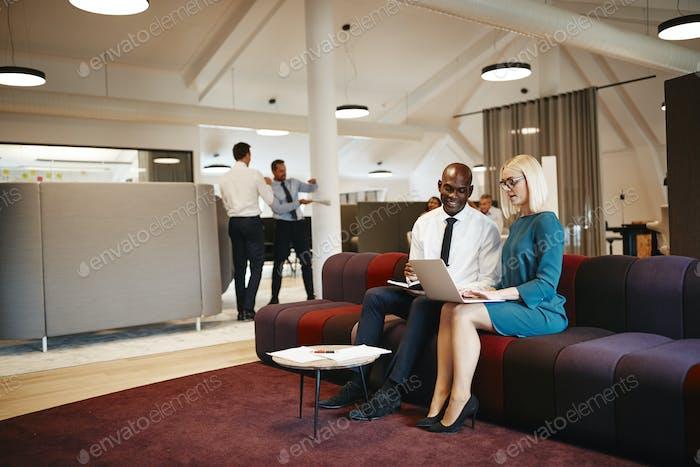 Empresarios diversos que Trabajo juntos en un sofá en una oficina