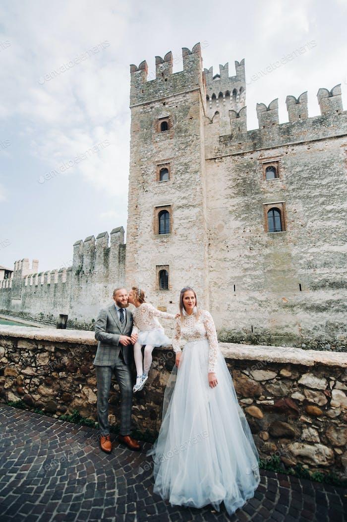 Eine glückliche junge Familie spaziert durch die Altstadt von Sirmione in Italien.Stilvolle Familie in Italien auf einem
