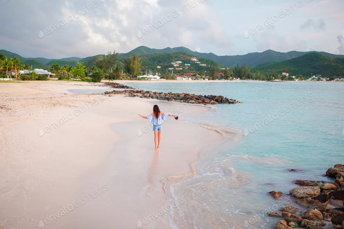 Young happy woman on white beach walking