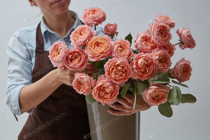 Female hands holding a vase with flowers of pink roses around a gray background. The concept of a