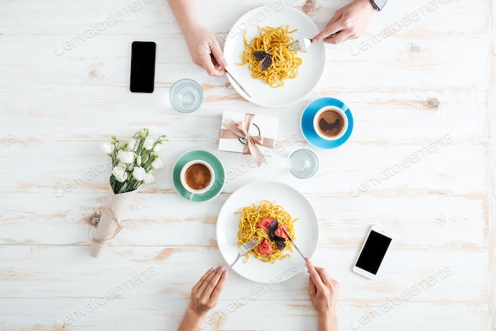 Hands of young couple eating pasta together on wooden table
