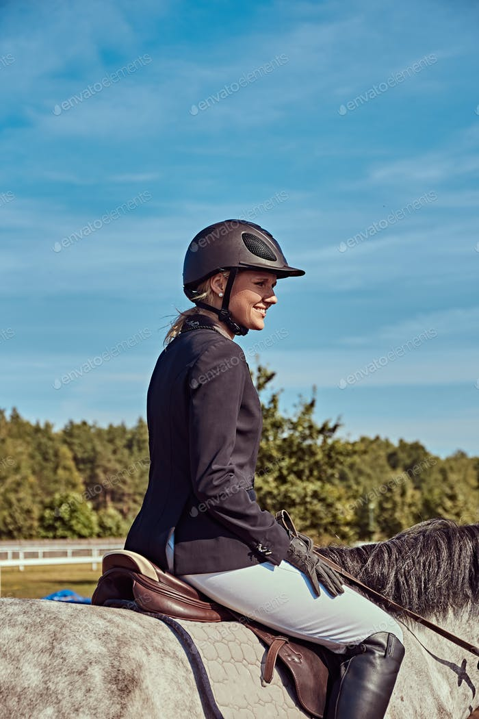 Portrait of a smiling female jockey on dapple gray horse in the open arena.