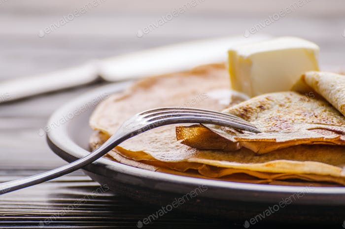 Stack of French crepes with butter in ceramic dish on wooden kit