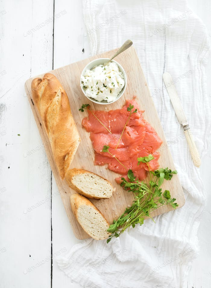 Salmon, ricotta and fresh parsley with baguette on a rustic wooden board