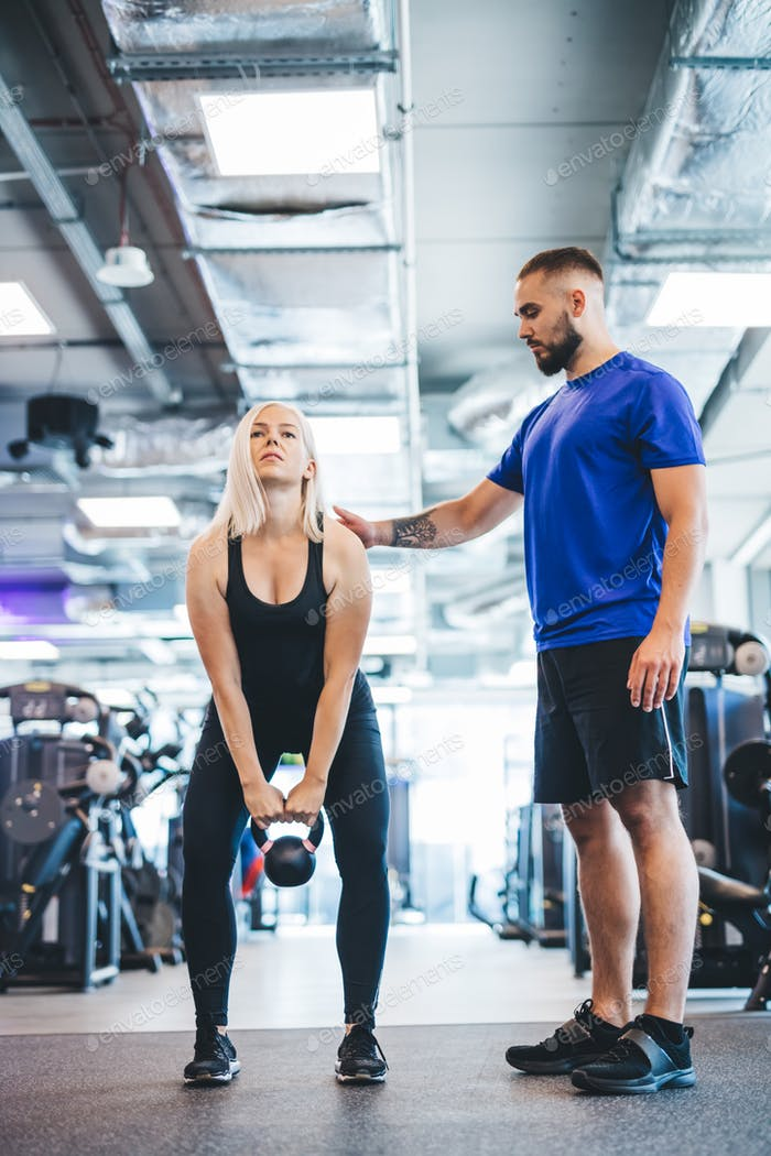 Woman working out with personal trainer at a gym.