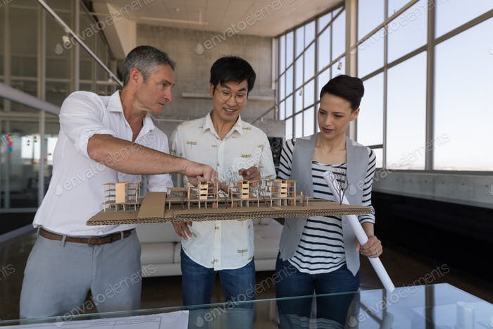 Side view of standing mixed race business colleagues discussing over house model in modern office