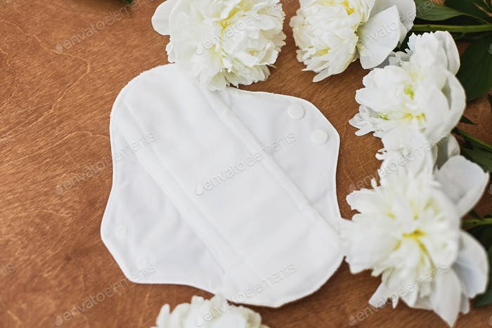 Reusable eco natural pad for menstrual days with peony flowers. White feminine washable