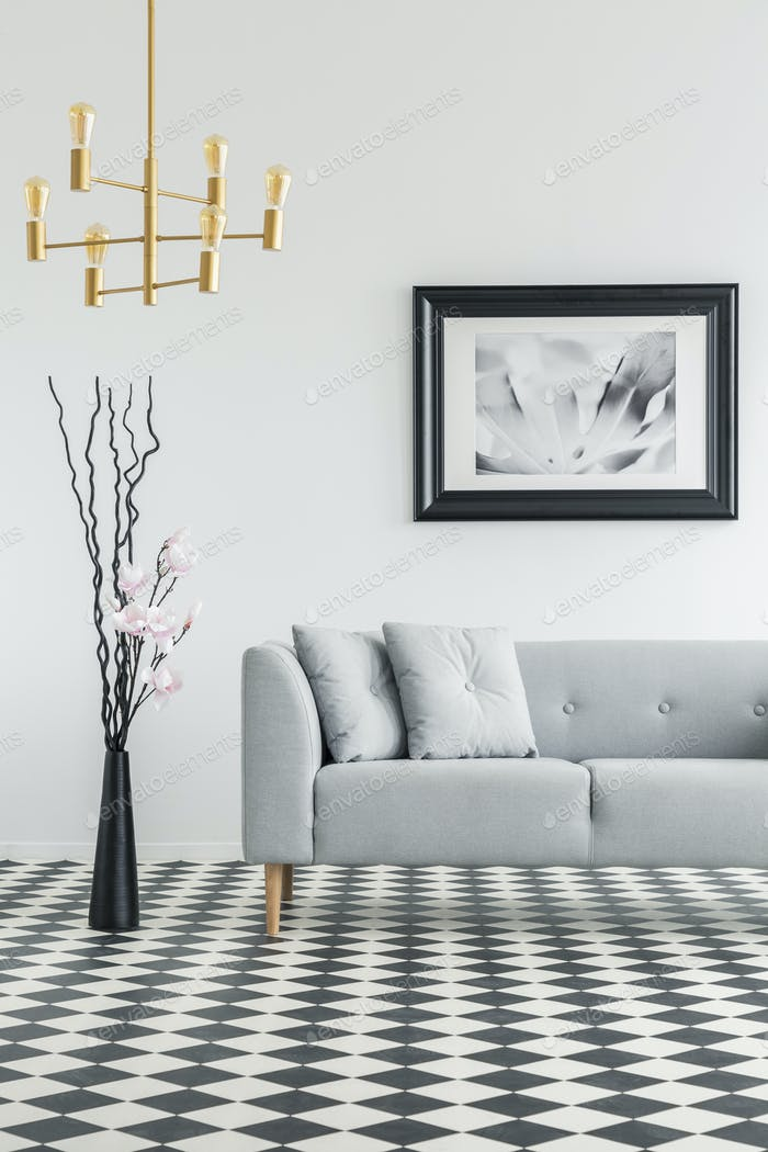 Plant next to grey couch in living room interior with checkered
