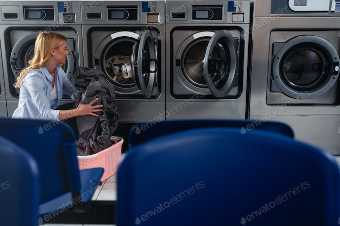Female doing laundry at laundromat