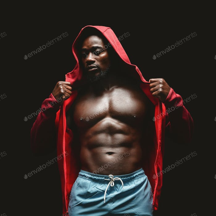 African boxer in red hoodie over black studio background