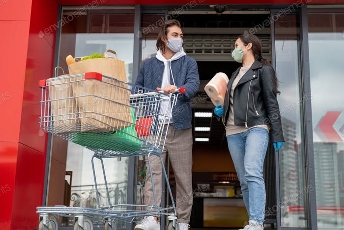 Young couple in protective masks leaving supermarket while man pushing cart