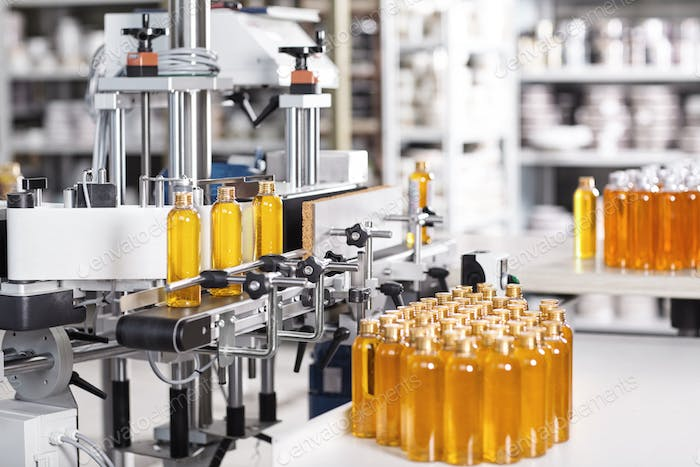 Bottles filled with soap yellow liquid standing on conveyor belt in factory. Automated process of cr