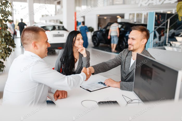 Manager and couple make out the sale of a new car