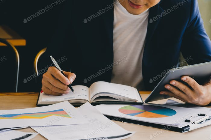 Businessman using tablet and analyzing investment charts