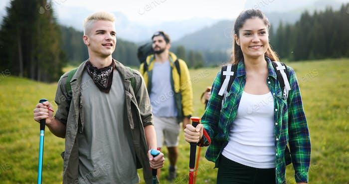 Vier glückliche Freunde schauen auf die Berge und haben Spaß zusammen