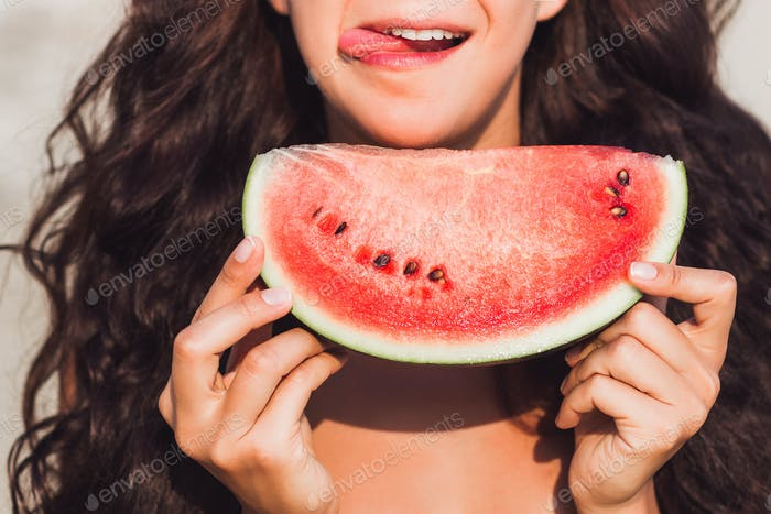 Girl eating a piece of watermelon with happy smile