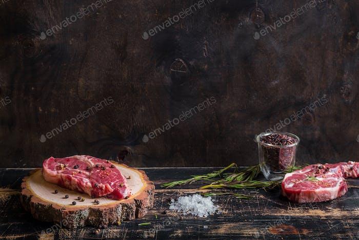 Rohes saftiges Fleischsteak auf dunklem Holzhintergrund zum Braten bereit
