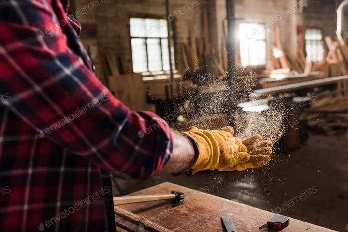 cropped shot of craftsman in protective gloves shaking off wooden chips from hands at sawmill