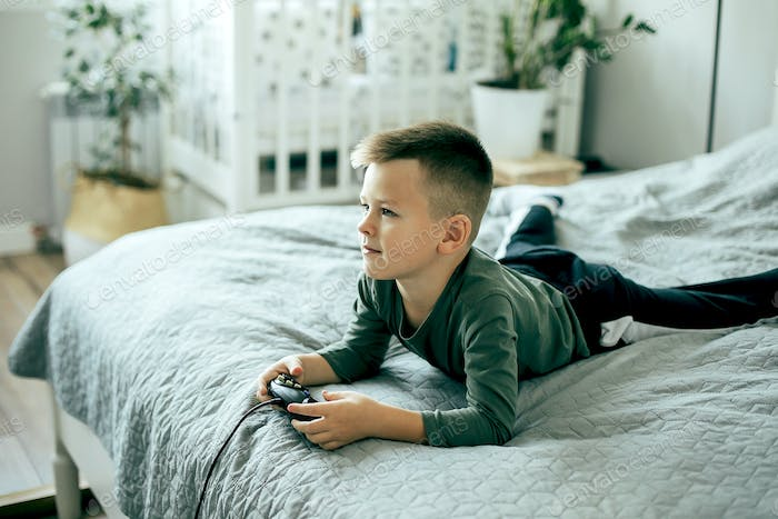 Caucasian little boy playing video games. Lifestyle, leisure concept