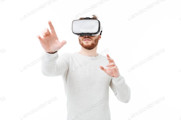 Portrait of young man in studio using virtual reality glasses over white background