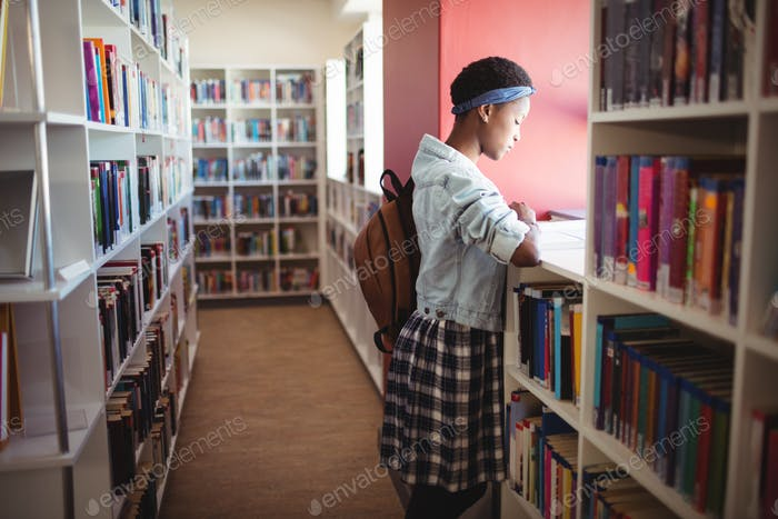 Attentive schoolgirl reading book in library