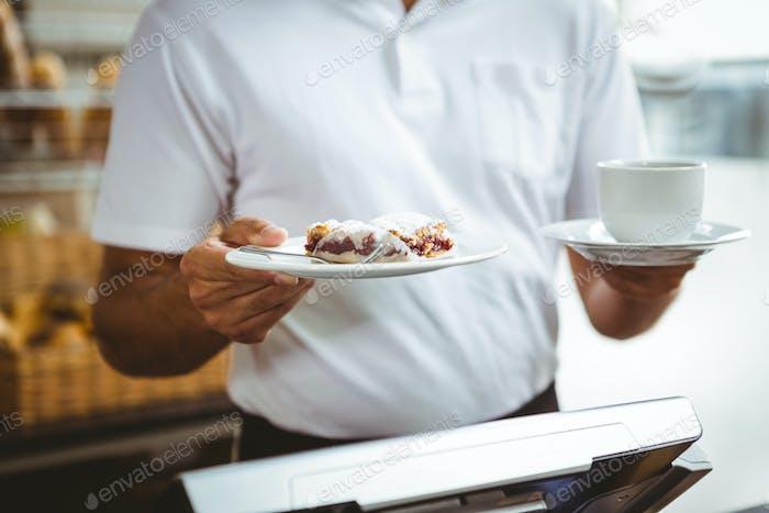 Smiling worker prepares breakfast at the bakery