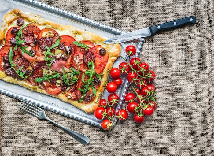 Homemade square pizza with meat, salami, cherry-tomatoes and fre