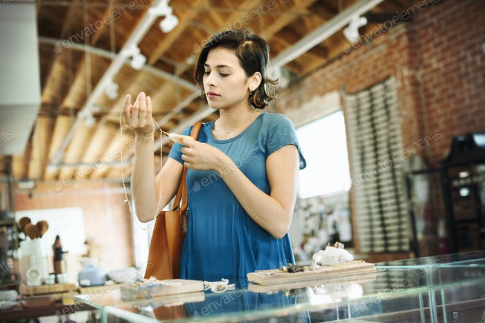 Young woman standing in a shop, looking at a necklace.
