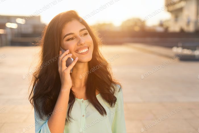Happy female student talking on phone, walking at sunset in city