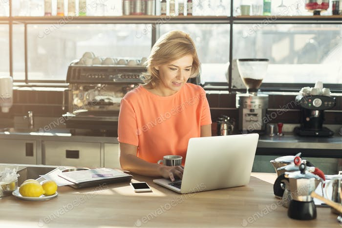 Happy middle-aged woman barista working on laptop